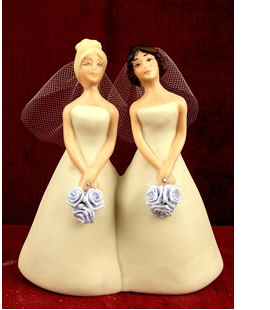 Picture of lesbian wedding cake toppers in their pretty light yellow bride gowns